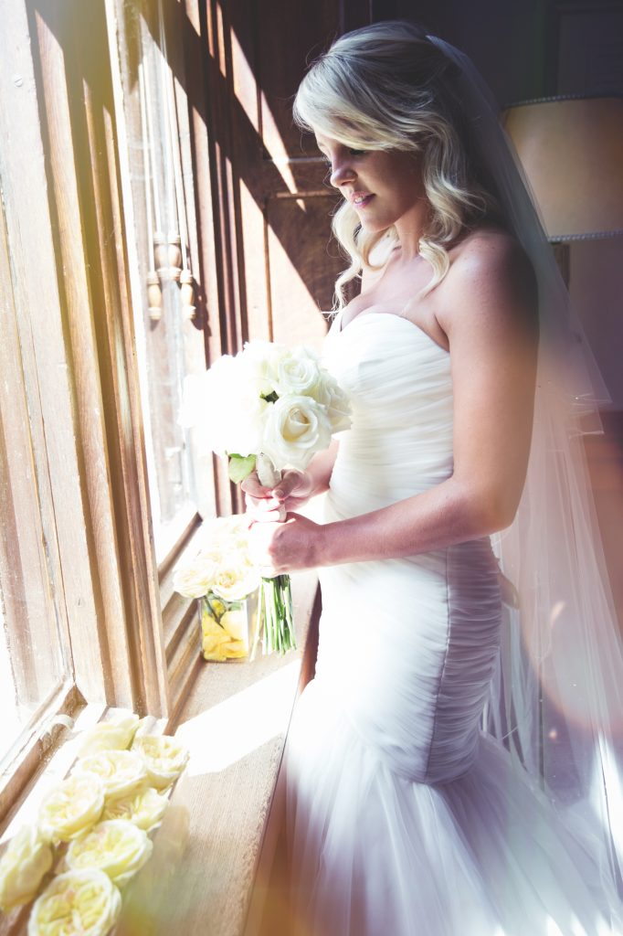 Bride in wedding dress at window in Nutfield priory