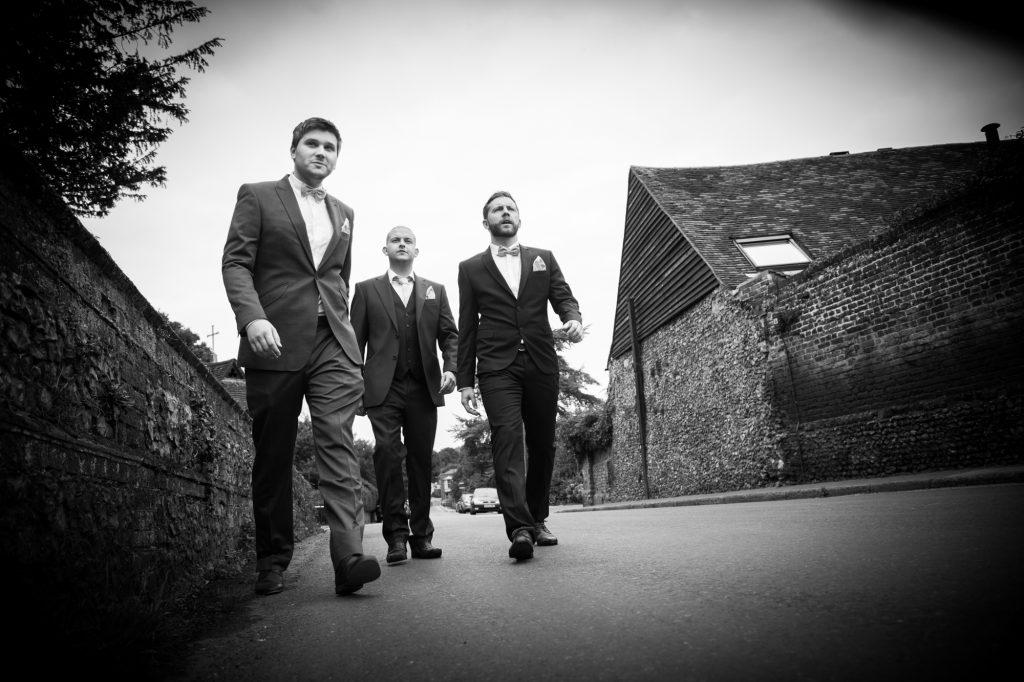 Groomsman walking fun photo at wedding
