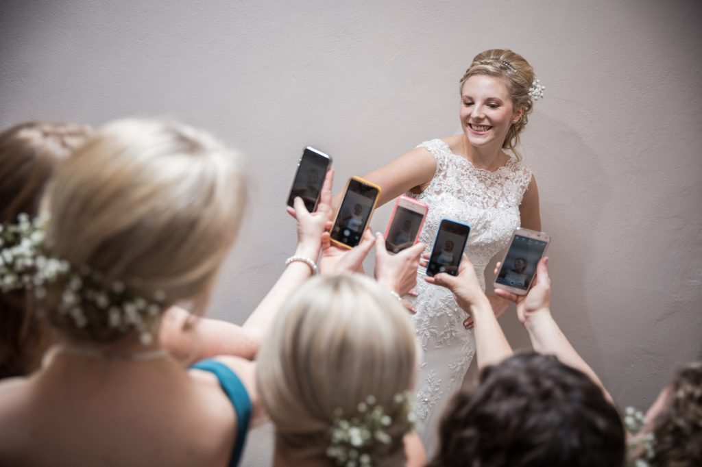 Wedding partying all taking photos of bride