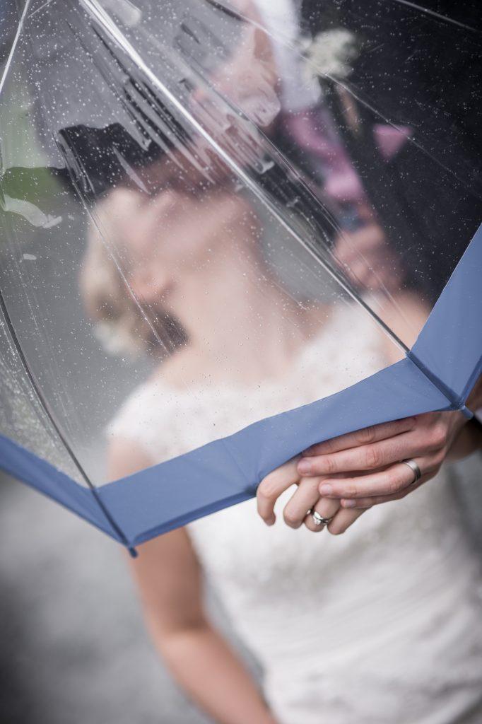 Bride and groom portrait through rain after wedding ceremony