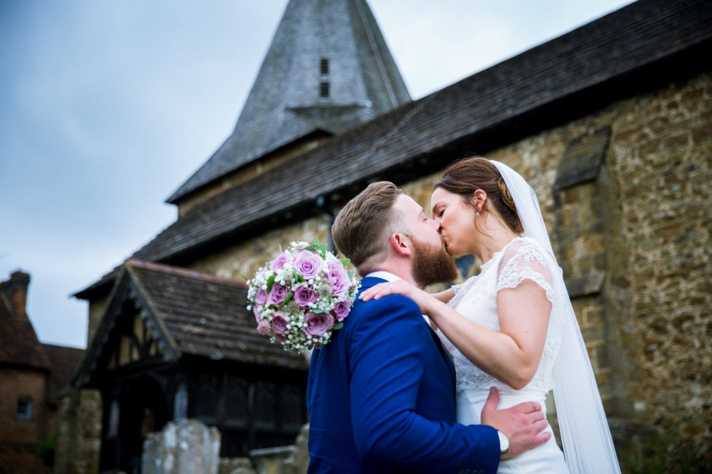 Bride and groom kissing outside of church after wedding ceremony