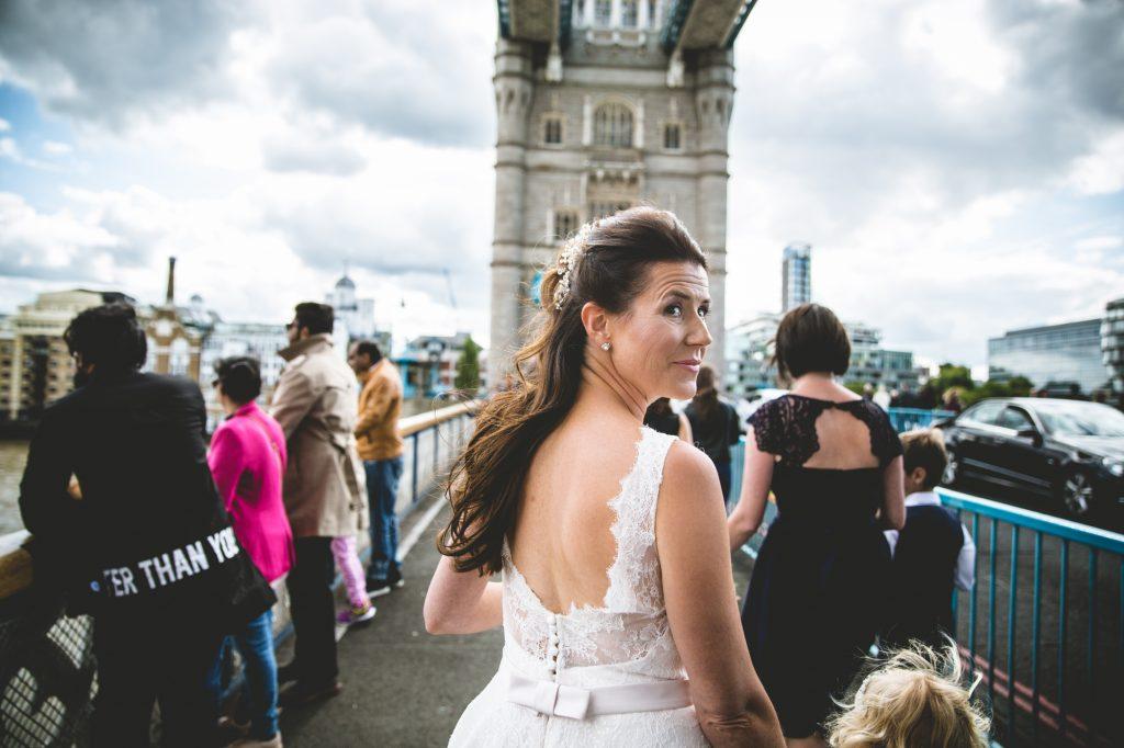 Bride walking over tower bridge in wedding dress
