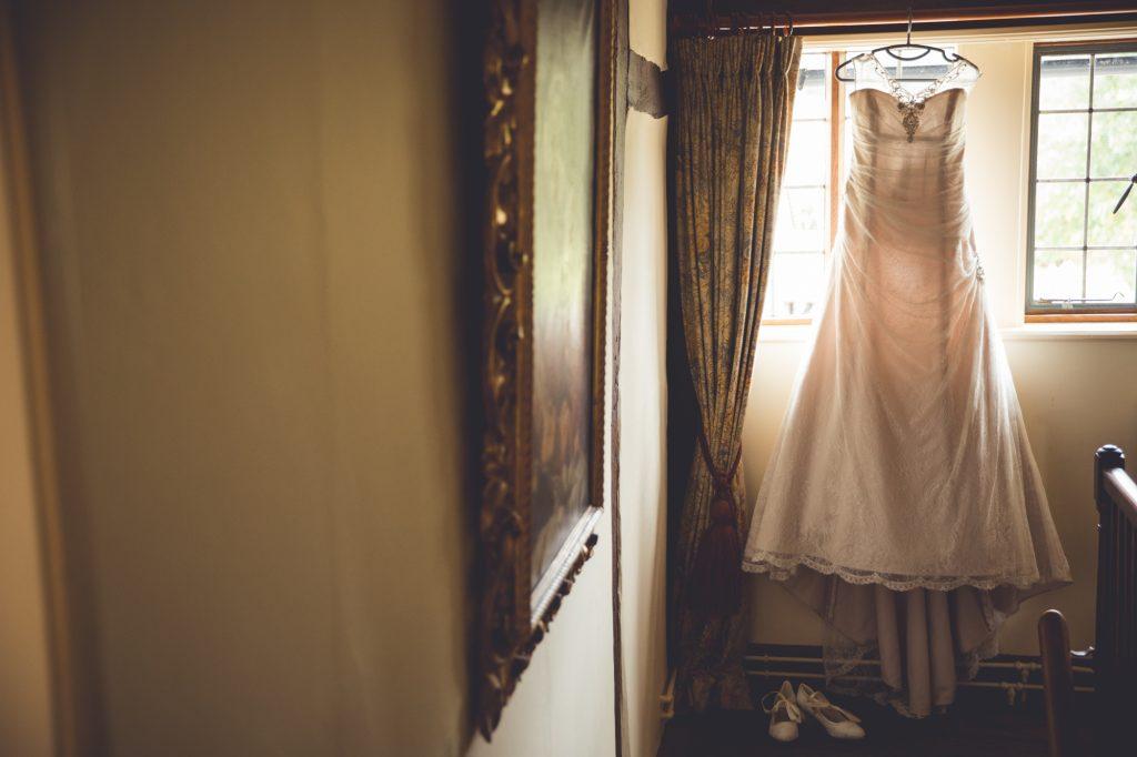 Hanging wedding dress in window photo at wedding preparation