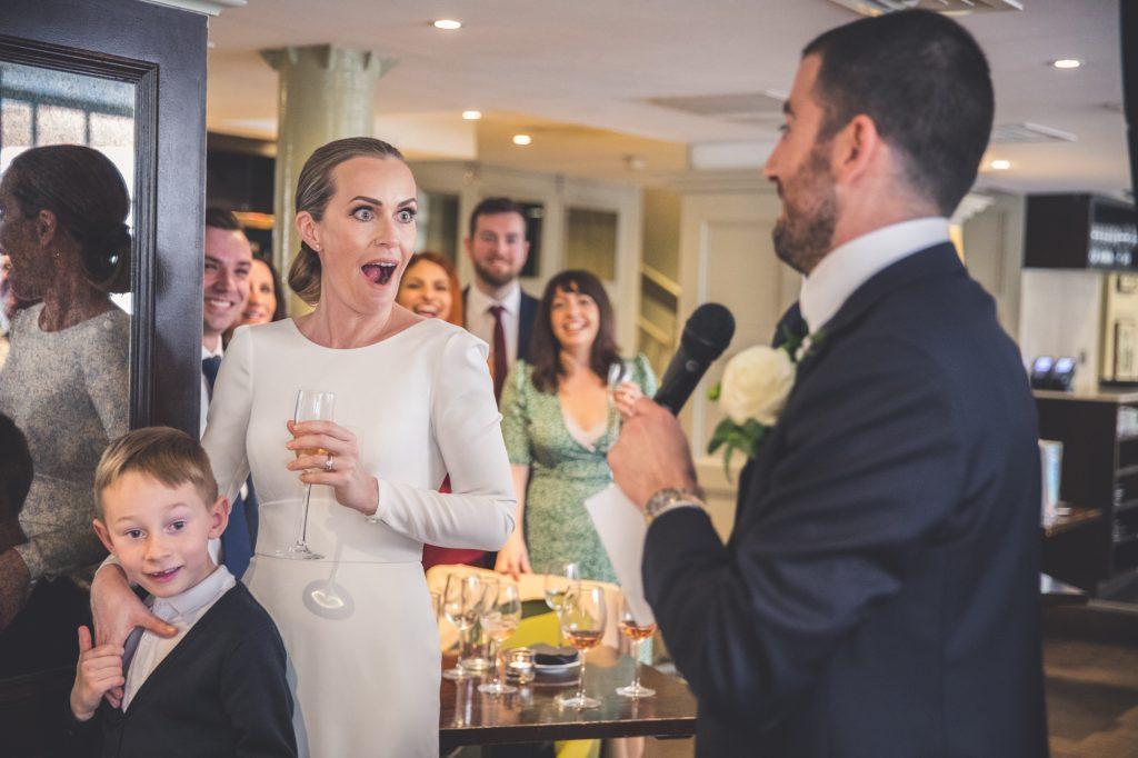 Wedding speeches photo bride looking shocked at grooms speech.