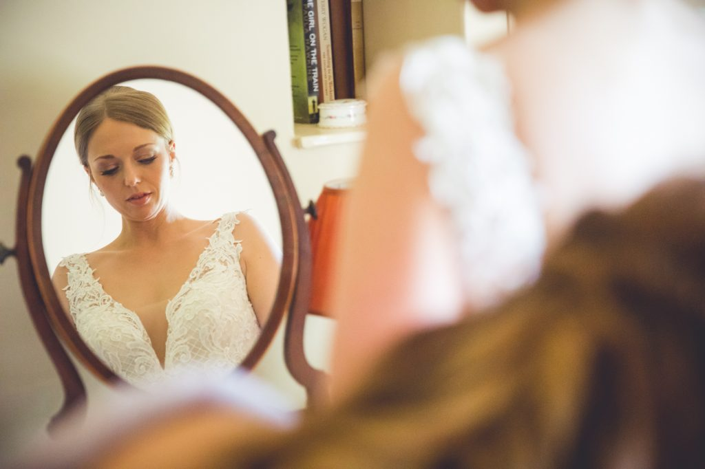 Bride getting into wedding dress in the mirror
