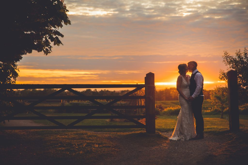 Bride and Groom portrait shot at a farm gate in the countryside at sunset.