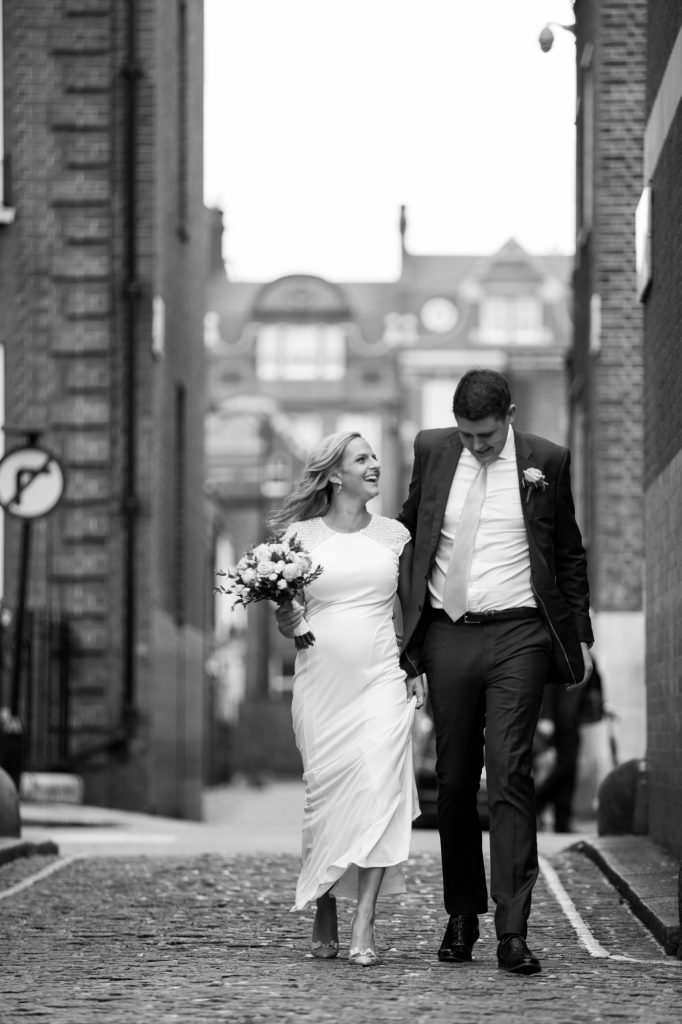 Bride and groom portrait after wedding ceremony walking through city