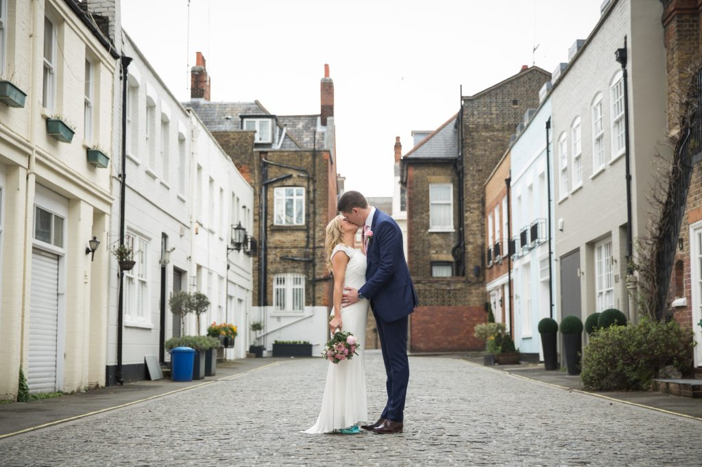 Bride and Groom portrait shot kissing on cobbled street in London.