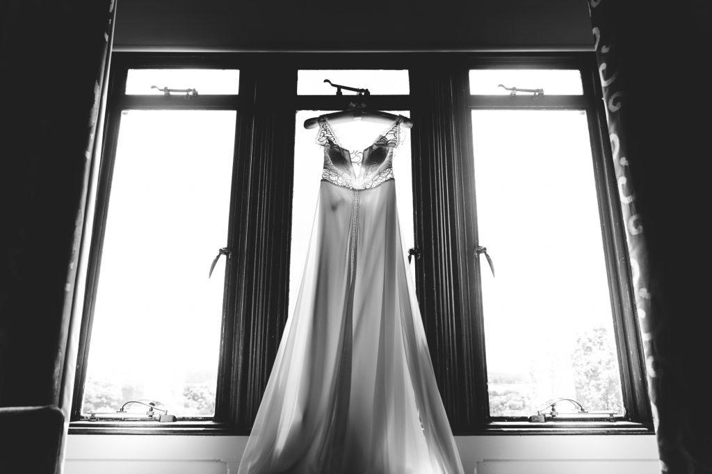 Hanging wedding dress in window photo