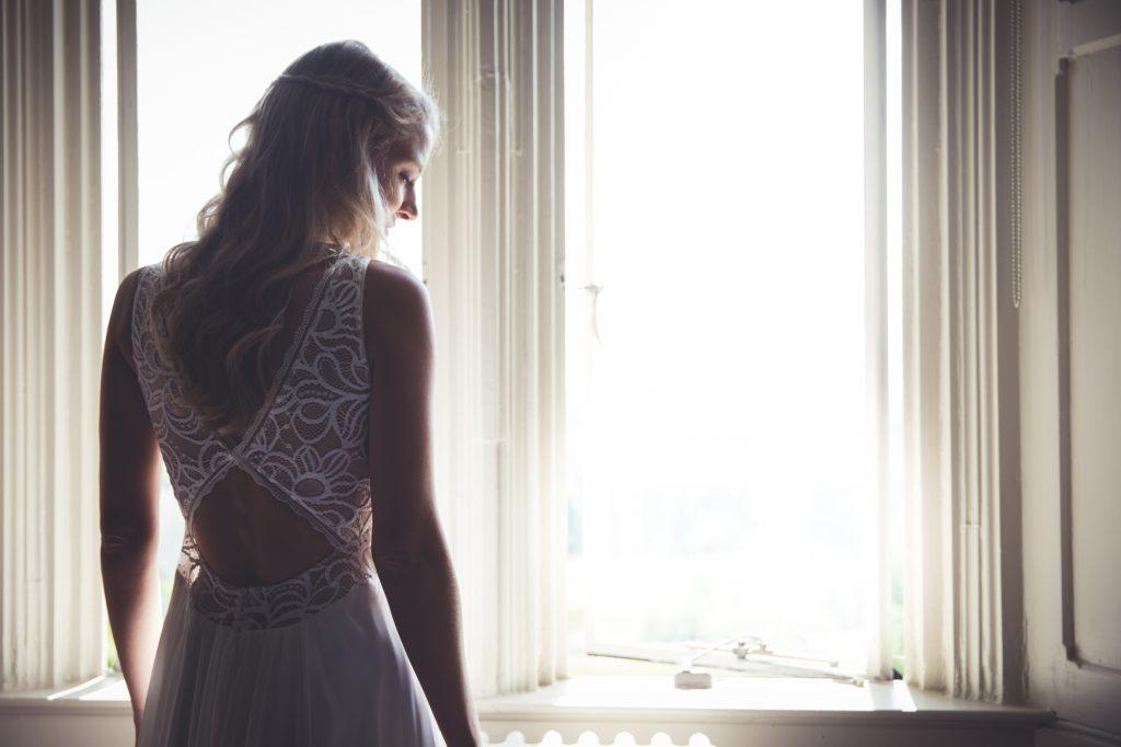 Bride standing in window in wedding dress