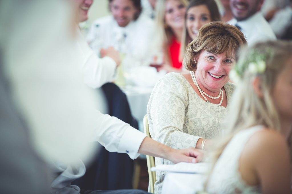 Mother of the groom laughing at the grooms wedding speech.
