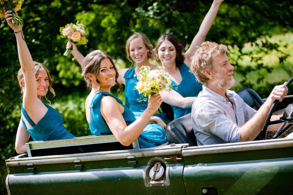 Bridal party in jeep on the way to the wedding