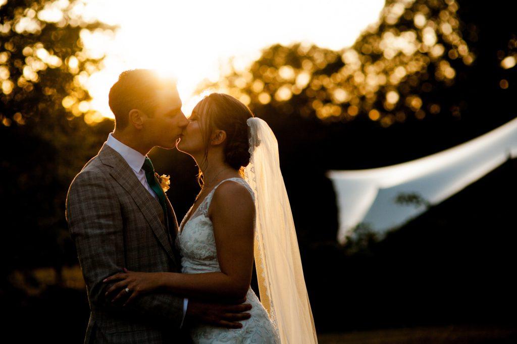 Bride and Groom portrait shot kissing at sunset.