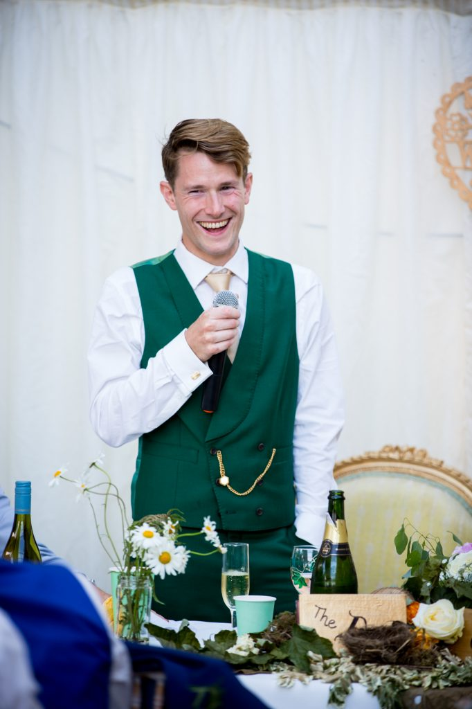 Groom laughing during his wedding speech.