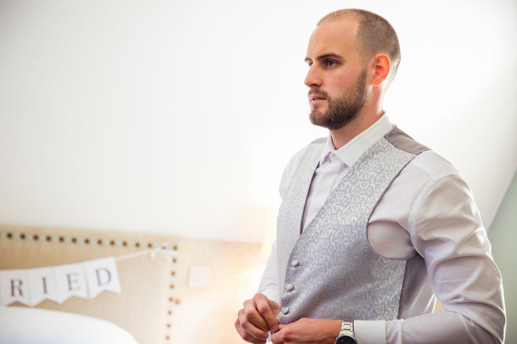 Wedding preparation photo groom putting on waistcoat