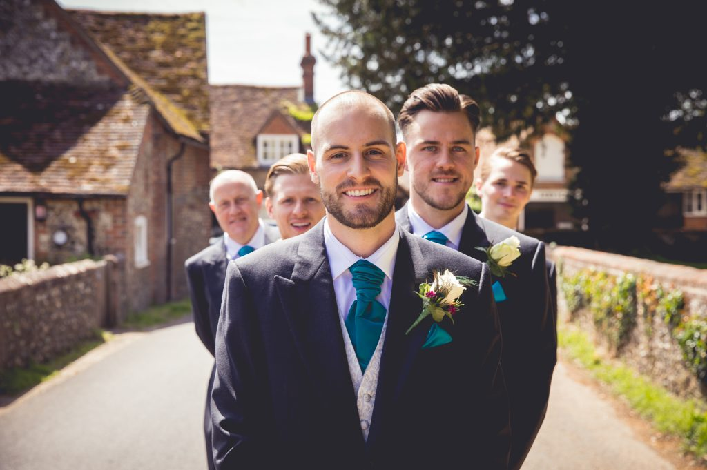 Fun groomsman photo wedding party looking at groom