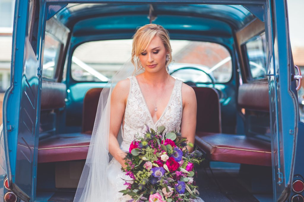 Bride in wedding dress in vintage car