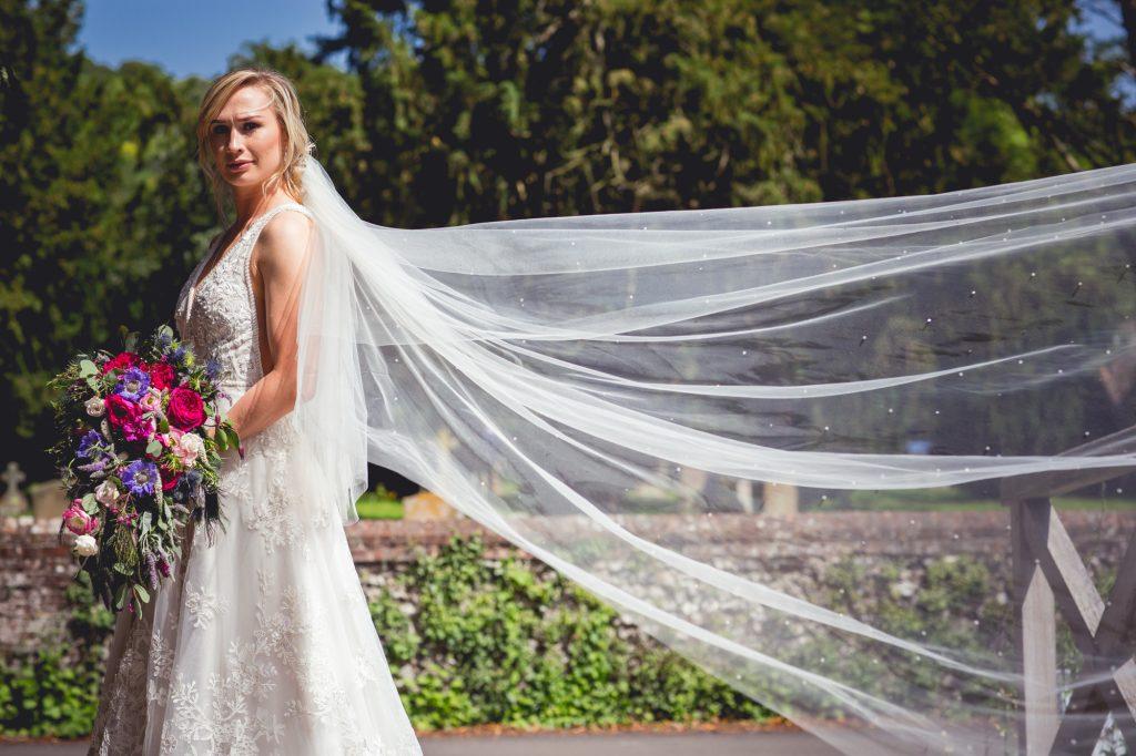 Bride portrait shot with veil flowing out.