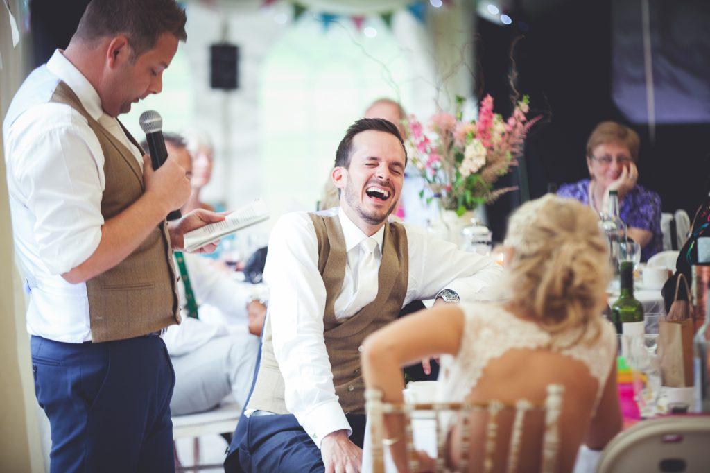 Groom laughing during the best man wedding speech.