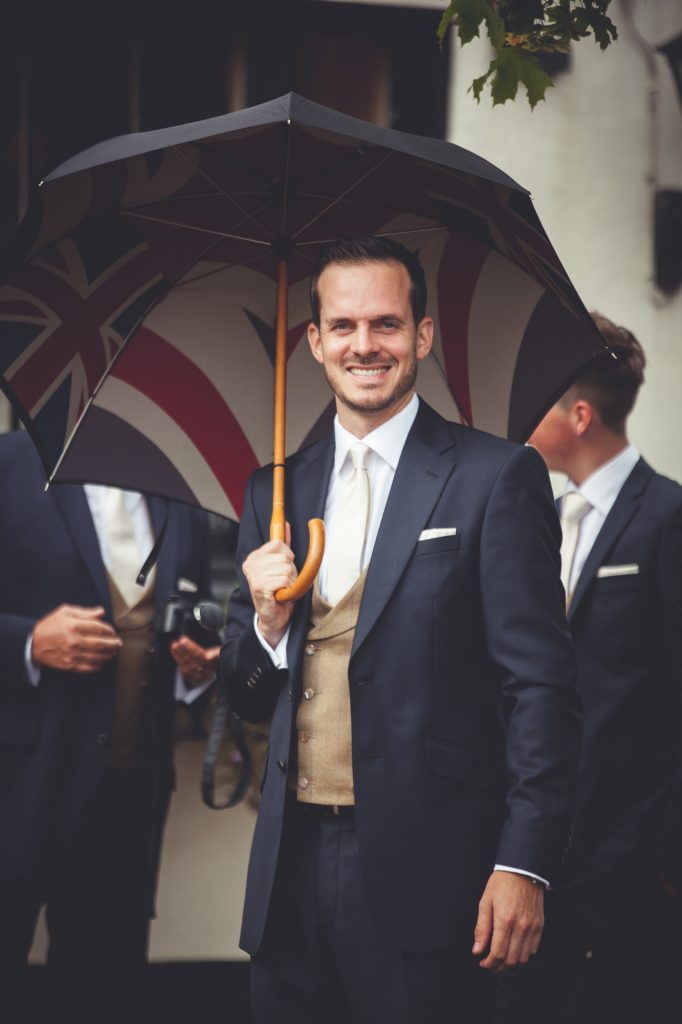Groom with umbrella before wedding