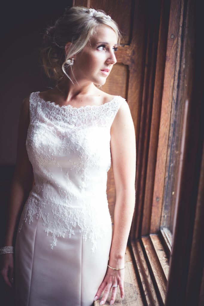 Bridal portrait in wedding dress looking out of window at Nutfield Priory