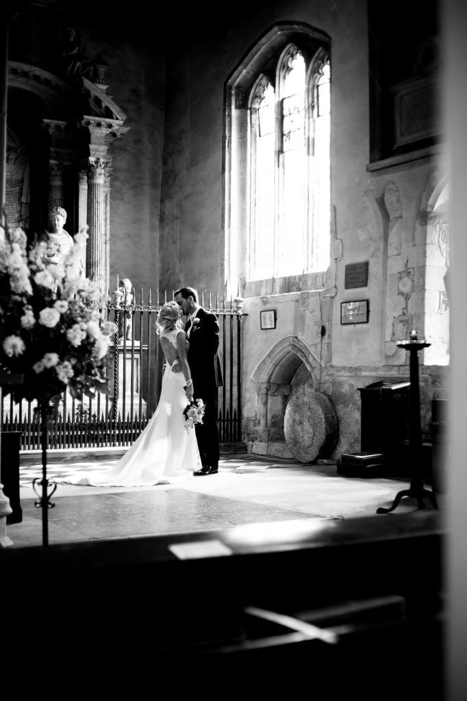 Bride and Groom portrait shot in the light streaming through the church window