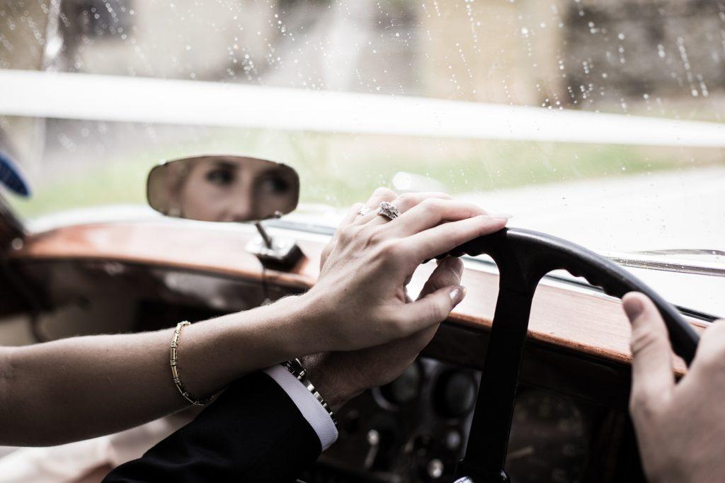 Bride and Groom portrait shot in a vintage car on wedding bands.