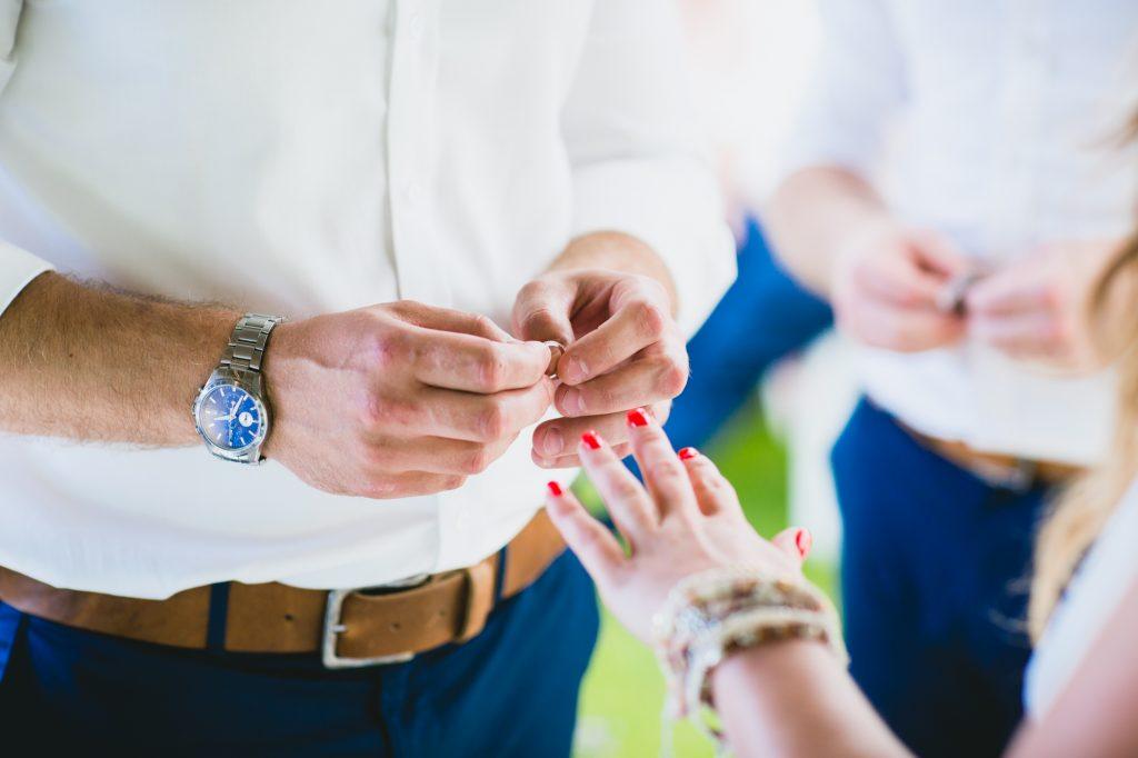 Groom putting ring on brides finger during wedding ceremony